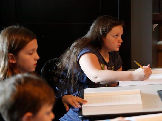Berkley Maschka, 9, works on math problems along side