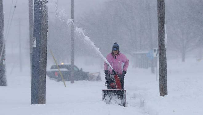 Heavy wet snow is the task of the day as a worker clears snow from in front of Pizza Ranch on Main Street Saturday, April 14, 2018 in Green Bay, Wis.