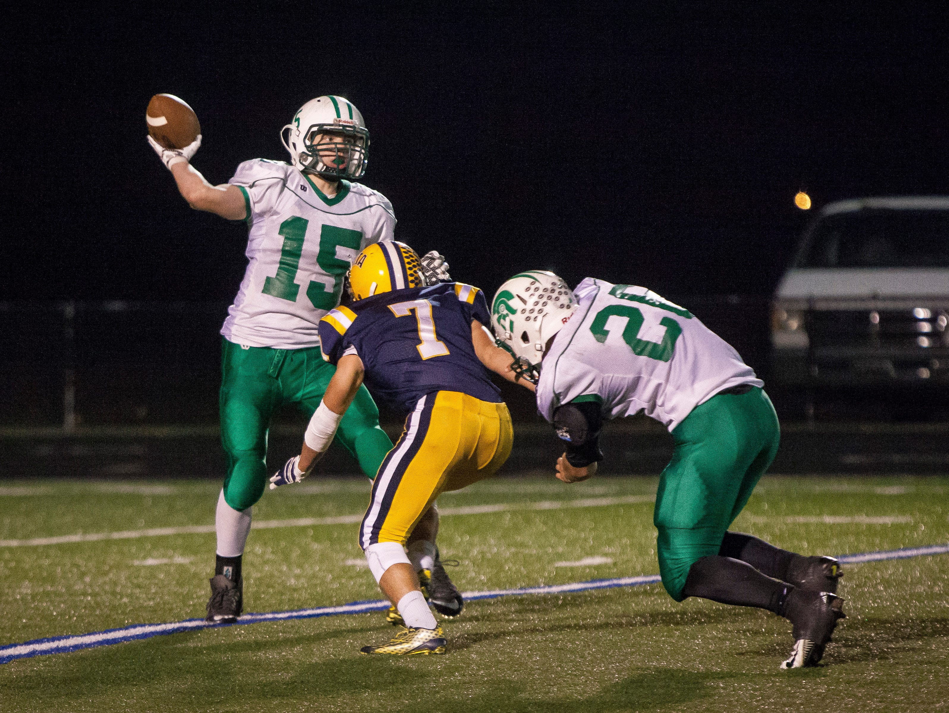 New Castle's Robbie Witham tries to throw the ball before being brought down by Delta's Blake Green Friday night at the Delta sectional game. Delta won 49-7.