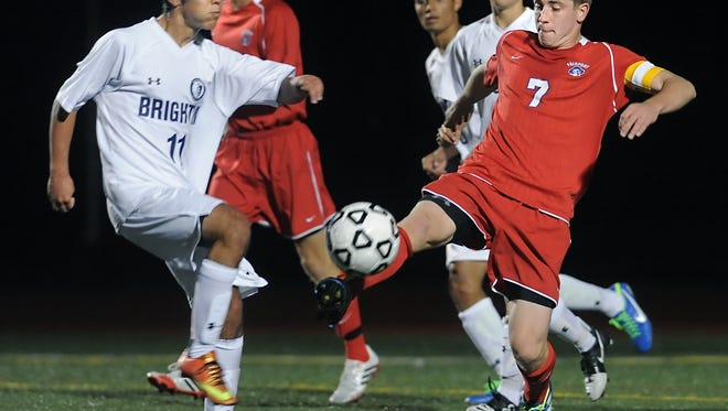 Fairport's Matt Bischoff, right, gets a foot on the ball before Brighton's Manny Gil can during a Monroe County boys soccer match played at Brighton High School on Monday, Sept. 23, 2013.  Fairport beat Brighton, 4-1.