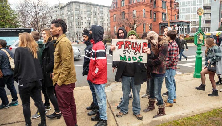 "Some people in line to receive free joints at the DCMJ #TRUMP420 event on Friday, Jan. 20, 2017 held up anti-Trump signs. One patron carried this sign, which says ""Trump Smokes Mids"" which asserts that Trump smokes mid-grade marijuana."