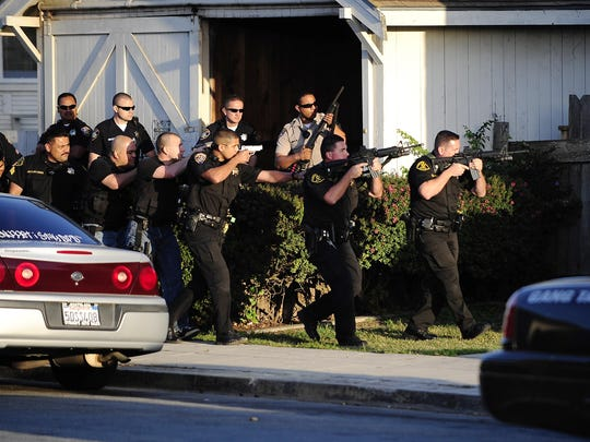 In this 2009 photo, the Salinas Police Violence Suppression Unit joins the Monterey County Gang Task Force surround an apartment on West San Luis Street in Salinas.