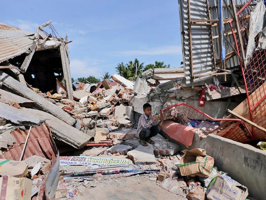 A boy sits on the rubble of a building that collapsed