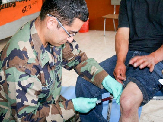 A physician's assistant Villalobos drains a painful knee at a clinic in Ecuador.