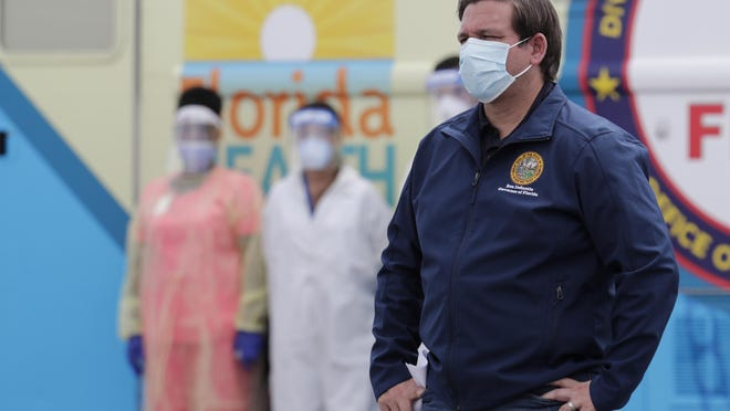 Florida Gov. Ron DeSantis wears a protective face mask during a news conference at a COVID-19 testing site at Hard Rock Stadium, during the new coronavirus pandemic, Wednesday, May 6, 2020, in Miami Gardens, Fla.