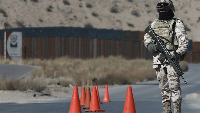A Mexican soldier stands guard at a checkpoint near the Mexico-U.S. border fence, on the Mexican side, separating the towns of Anapra, Mexico, and Sunland Park, N.M., on Jan. 25, 2017.