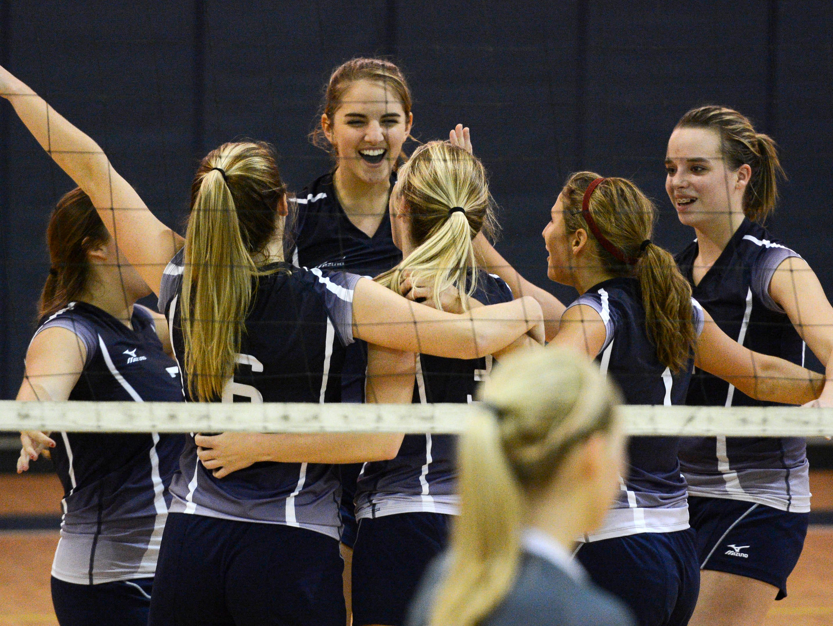 """Merritt Island Christian players celebrate their straight set victory over Trinity Christian during Tuesday""""s regional quarterfinal volleyball match."""