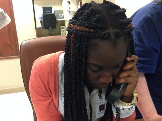 Raymonde Armoo answers the phone while volunteering at Christus St. Frances Cabrini Hospital.