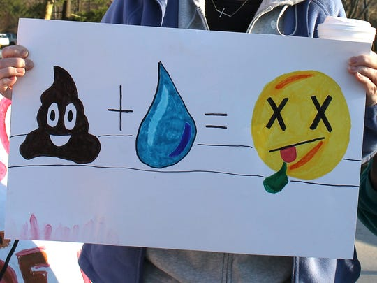 A woman uses emojis on her sign to convey her feelings towards an increase in chicken houses on Delmarva.