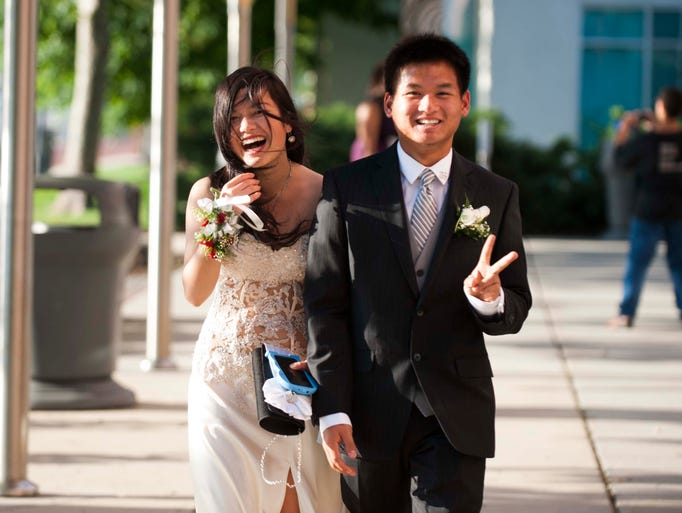 Annie Zheng and Tin Luu make their way to the Cherry Hill West Prom at Adventure Aquarium, June 5, 2014 in Camden.