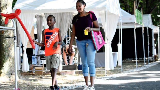 Nicole Friend, right, walks with her son Nehemiah Davis, 9, both of York City, during Yorkfest Fine Arts Festival in York City, Sunday, Aug. 28, 2016. Dawn J. Sagert photo