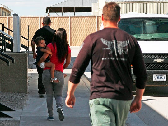 A woman and child are escorted to a van by detention facility guards inside the Artesia Family Residential Center, a federal detention facility for undocumented immigrant mothers and children in Artesia, N.M, Sept. 10, 2014.