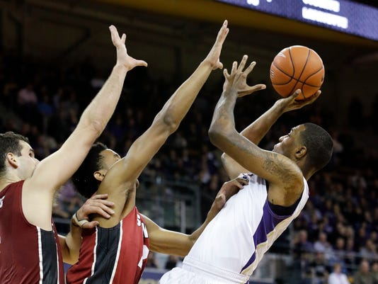Stanford's Stefan Nastic (4) and Anthony Brown defends Washington's Quevyn Winters during the first half of an NCAA college basketball game Wednesday, Jan. 28, 2015, in Seattle. (AP Photo/Elaine Thompson)