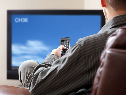 A man watching TV while sitting on a couch