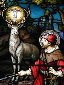 A stained glass window featuring St. Hubert at the moment of his epiphany where he saw the crucifix suspended between the stag's antlers.