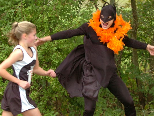 York Suburban senior Joe Bentz sports a Batman costume as he cheers on junior Emily Perina on the way to her first place finish in the YAIAA Cross Country championships at John Rudy Park on Thursday, Oct. 20, 2005. YORK DAILY RECORD/SUNDAY NEWS-JASON PLOTKIN
