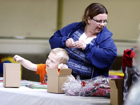 Robert Seymour, 4, or Corning, places a ticket in a gift bag raffle box for his mother, Cassie, Saturday at the 12th annual Rene Jones Buddy Walk at Eldridge Park.
