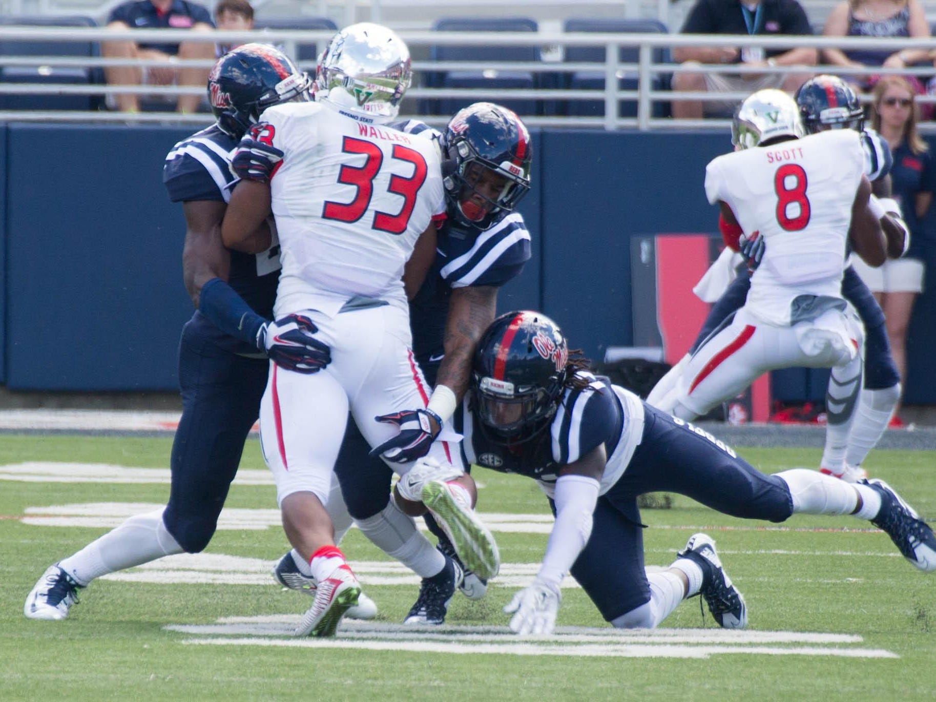 Ole Miss defensive backs Trae Elston, Channing Ward, and Maquis Haynes stop Fresno State's Marteze Waller on third down in the red zone.