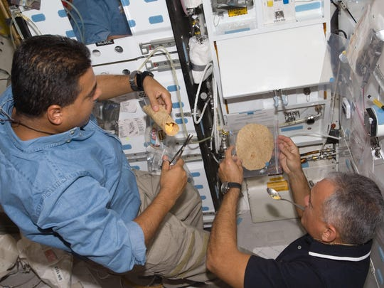 "STS-128 Mission Specialists Jose Hernandez (left) and John ""Danny"" Olivas prepare food near the galley on the middeck of space shuttle Discovery after undocking with the International Space Station."