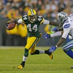 Green Bay Packers running back James Starks (44) makes a catch and runs upfield as Dallas Cowboys middle linebacker Rolando McClain (55) tries to tackle him at Lambeau Field.