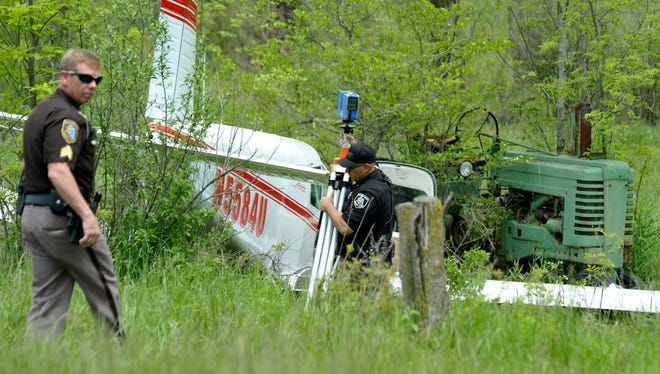 Macomb County Sheriff's deputies investigate a single-engine plane crash in a field across from the Ray Community Airport.