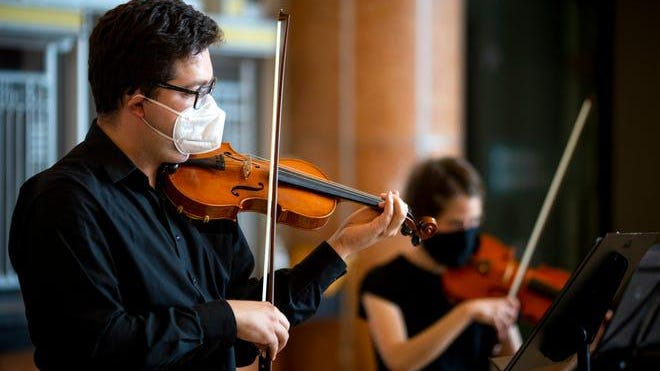 Members of the Cincinnati Symphony Orchestra wear masks as they perform inside Union Terminal on Friday, July 17, 2020, to celebrate the reopening of the Cincinnati Museum Center to the public after the center was closed for four months due to COVID-19.