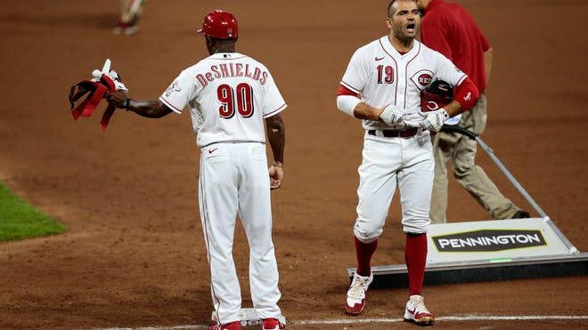 Cincinnati Reds first baseman Joey Votto (19), right, shouts in frustration after lining out to end the third inning of the National League game between the Reds and the Chicago Cubs at Great American Ball Park in Cincinnati on Monday July 27, 2020.