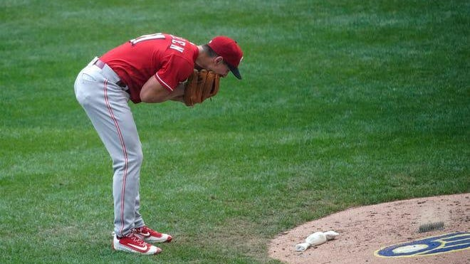 Cincinnati Reds relief pitcher Michael Lorenzen yells into his glove after giving up his second bases loaded walk during the sixth inning of a baseball game against the Milwaukee Brewers Sunday, Aug. 9, 2020, in Milwaukee.