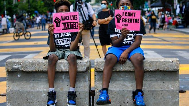 "In this June 24, 2020, file photo, Tyshawn, 9, left, and his brother Tyler, 11, right, of Baltimore, hold signs saying ""Black Lives Matter"" and ""I Can't Breathe"" as they sit on a concrete barrier near a police line as demonstrators protest along a section of 16th Street that has been renamed Black Lives Matter Plaza in Washington. Thousands of Black activists from across the U.S. will hold the 2020 Black National Convention on Aug. 28, 2020, via livestream to produce a new political agenda that builds on the protests that followed George Floyd's death."