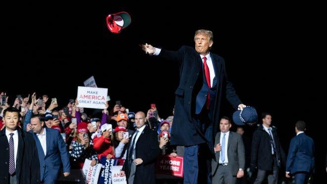 President Donald Trump tosses a hat to supporters as he arrives to speak at a campaign rally at Duluth International Airport, Wednesday, Sept. 30 2020.