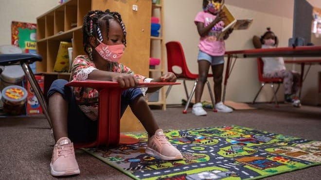 Alonah Montgomery sits on the floor socially distanced from other children while going over a lesson as Laiyah Singletery reads at Pippen Palace Childcare Academy on Detroit's west side on Aug. 13, 2020. The business has required the wearing of masks and had has installed hands free soap and hand sanitizer dispensers as well as other items to practice social distancing to fight the spread of COVID 19 at the facility.