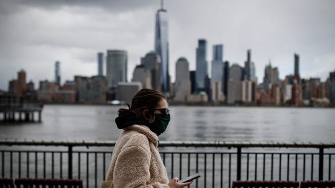 A woman wearing a face mask walks along the Jersey City waterfront with the New York City skyline in the background on April 10.