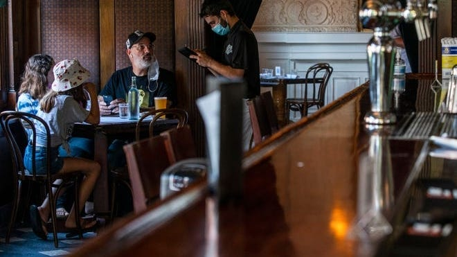 A waiter in a face mask takes the order of customers inside a local restaurant during lunch during the coronavirus pandemic on Friday, Sept. 4, 2020, in Hoboken, N.J.  [Eduardo Munoz Alvarez, AP]