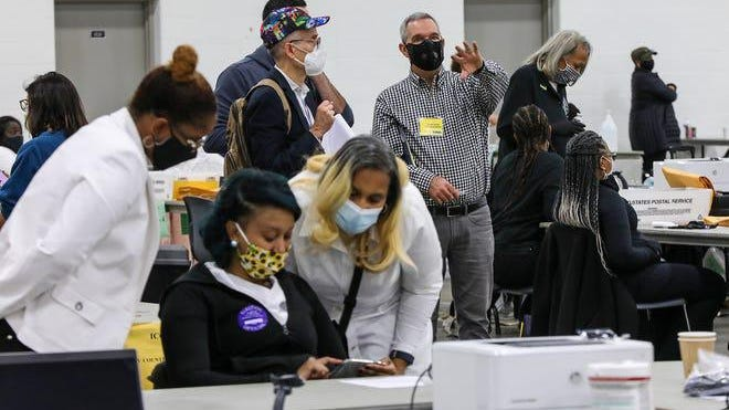 Election challengers watch as election officials process absentee ballots in the Detroit Elections Department Absentee Ballot counting room at TCF Center in Downtown Detroit on Wednesday, Nov. 4, 2020.