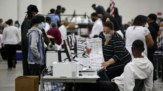 Poll workers count absentee ballots at the TCF Center on Tuesday, Nov. 3, 2020 in Detroit.