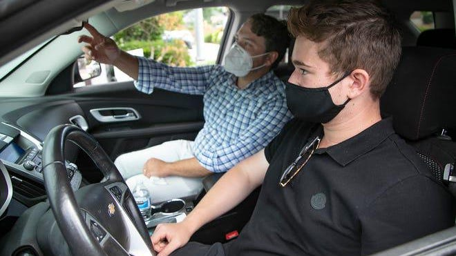 Benny Malburg, 33, President and Owner of Official Driving School, left, works with Asher Meltzer, 15, of Bloomfield Hills after he finishes his day of driver training at their headquarters in Royal Oak Thursday, July 23, 2020.