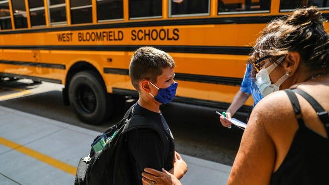 Teachers help a student find his correct bus after his first day of school at Sheiko Elementary School in West Bloomfield, Mich. on Aug. 27, 2020.  Sheiko split the day up into two groups, a morning and an afternoon, to create smaller classes.