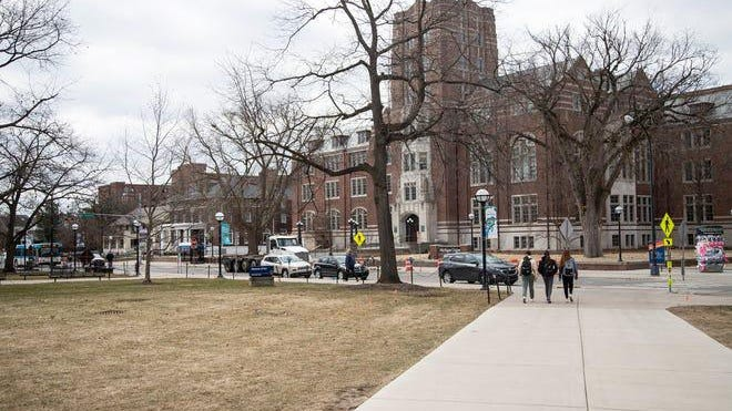 Three students walk toward the Michigan building on the University of Michigan campus in Ann Arbor Tuesday, March 17, 2020.