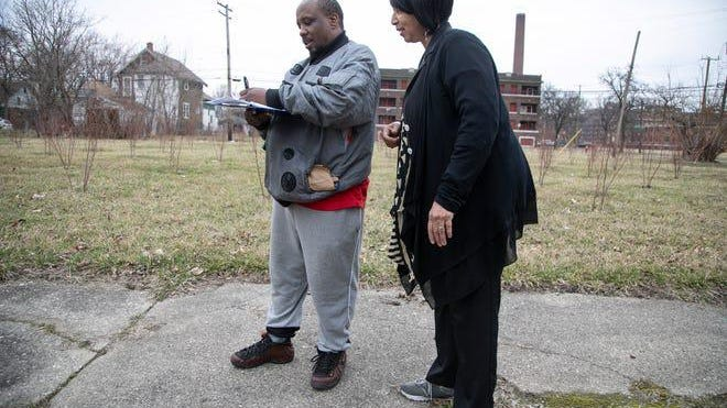 Frederick Campbell, 45, signs a petition handed to him from Venita Thompkins, 55, Thursday, March 12, 2020. Thompkins encouraged Campbell to attend a zoning meeting to be held at Detroit City Hall later in March to oppose the developer of Detroit's Herman Kiefer Complex who is proposing a tree nursery on vacant land surrounding the development. Some residents are opposed to the plan they say the nursery won't benefit the neighbors that is only in the economic interest of the developer.