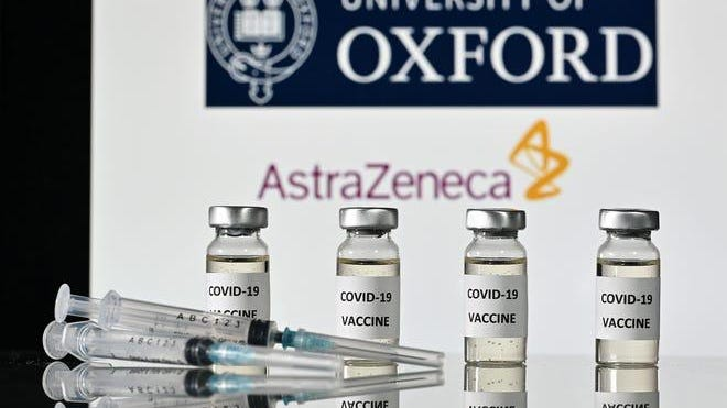 h.Vials with COVID-19 vaccine stickers attached and syringes are pictured in front of University of Oxford and AstraZeneca logos.