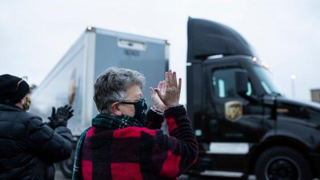 Susan Deur of Plainwell, center, and Nancy Galloway of Plainwell, left, applaud and cheer as they watch the trucks carrying Covid-19 vaccine leave at Pfizer Global Supply in Portage, Mich., Sunday, Dec. 13, 2020.