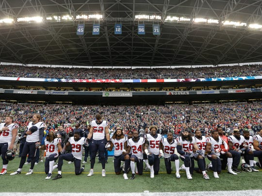"Houston Texans players kneel and stand during the singing of the national anthem before an NFL football game last Oct. 29 against the Seattle Seahawks, in Seattle. NFL owners have approved a new policy aimed at addressing the firestorm over national anthem protests, permitting players to stay in the locker room during the ""The Star-Spangled Banner"" but requiring them to stand if they come to the field. The decision was announced Wednesday."