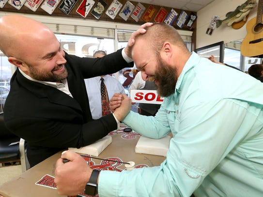 Jason Gulley, left, a professional arm wrestler taunts