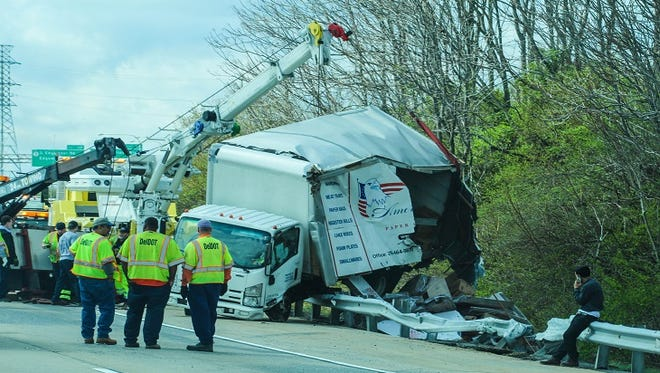 Crews clean up a box truck on Interstate 495 Monday. The crash caused extensive delays.
