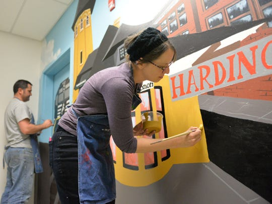 More than 100 volunteers from Wells Fargo spent Saturday morning, November 4, 2017, upgrading Harding  Elementary School. From left, Corby Shuey, art teacher at Lebanon Senior High School, and his wife Kelly put the finishing touches on a mural depicting a scene from the City of Lebanon 100 years ago. The mural includes Harding Elementary School which will celebrate it's 100th year in 2018.