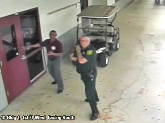 This Feb. 14, 2018, frame from security video provided by the Broward County Sheriff's Office shows deputy Scot Peterson, right, outside Marjory Stoneman Douglas High School in Parkland, Fla. The video released Thursday, March 15, shows Peterson going toward the high school building while a gunman massacred 17 students and staff members, but stayed outside with his handgun drawn.