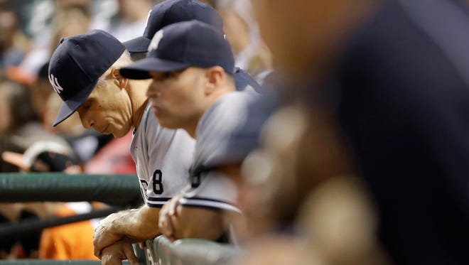 New York Yankees manager Joe Girardi, left, stands in the dugout in the second inning of a baseball game against the Baltimore Orioles in Baltimore, Saturday, Sept. 3, 2016.