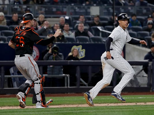 New York Yankees' Giancarlo Stanton, right, moves away from Baltimore Orioles catcher Caleb Joseph (36) in a rundown on ball hit by New York Yankees' Neil Walker during the sixth inning of a baseball game, Friday, April 6, 2018, in New York. Stanton was out on the play. (AP Photo/Julie Jacobson)
