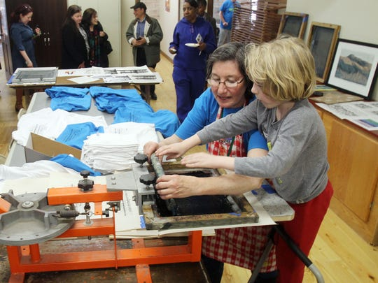 Anita Kiewra shows Jack Budnik, 5, the art of silk screening in the artists studios, during the grand opening of the new Poughkeepsie Underwear Factory on North Cherry Street in downtown Poughkeepsie March 30, 2017.