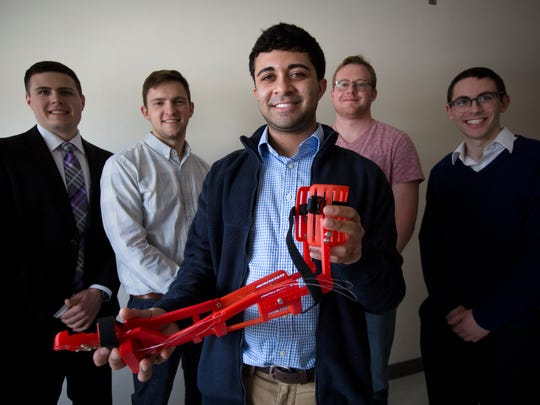 Tue., Feb. 14, 2017: Ishan Anand, a fourth-year biomedical engineering student at the University of Cincinnati, holds a 3D-printed prosthetic that Enable UC, a student organization, produced. Behind him, are other biomedical engineering students that are part of Enable UC. From left: Nick Bailey, Jacob Knorr, Derryn Scott, and Yosef Kirschner.